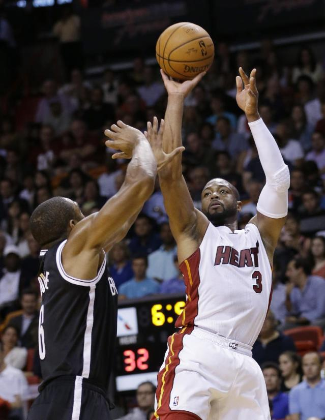 Miami Heat guard Dwyane Wade (3) takes a shot against Brooklyn Nets forward Alan Anderson (6) during the first half of an NBA basketball game, Wednesday, March 12, 2014, in Miami. (AP Photo/Wilfredo Lee)