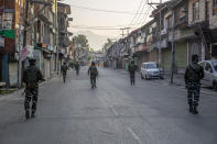 Indian paramilitary soldiers patrol a deserted street on the first anniversary of India's decision to revoke the disputed region's semi-autonomy, in Srinagar, Indian controlled Kashmir, Wednesday, Aug. 5, 2020. Last year on Aug. 5, India's Hindu-nationalist-led government of Prime Minister Narendra Modi stripped Jammu-Kashmir of its statehood and divided it into two federally governed territories. Late Tuesday, authorities lifted a curfew in Srinagar but said restrictions on public movement, transport and commercial activities would continue because of the coronavirus pandemic. (AP Photo/ Dar Yasin)