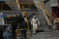 A healthcare worker descends a flight of stairs during a house-to-house campaign to help curb the spread of the new coronavirus in the Mallasa neighborhood of La Paz, Bolivia, Saturday, Aug. 8, 2020. (AP Photo/Juan Karita)