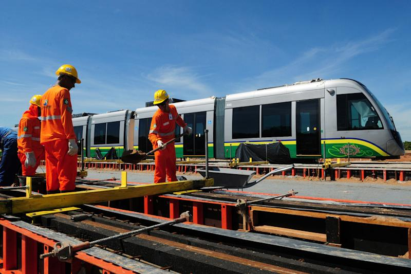 In this Nov. 13, 2013 photo released by Secom-MT, personnel work next to new trains in Cuiaba, Mato Grosso state, Brazil. The head of World Cup projects for Brazil's far-western Mato Grosso state has acknowledged the light rail system in the city of Cuiaba meant to help football fans move around the city during World Cup matches won't be ready in time for the 2014 World Cup. (AP Photo/Secom MT, Josi Pettengill)