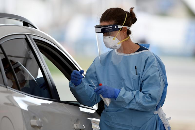 A medical worker performs a COVID-19 test on members of the public at the Bondi Beach drive-through test centre. Source: AAP