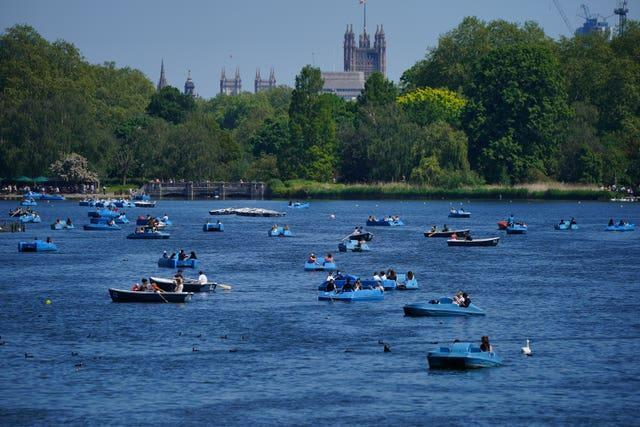 People ride pedalos on the Serpentine in Hyde Park, London