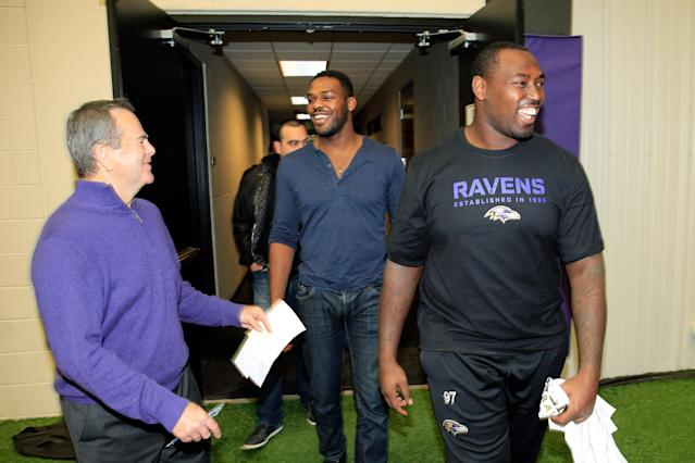 OWINGS MILLS, MD - NOVEMBER 13: UFC fighter Jon Jones (L) and his brother defensive end Arthur Jones #97 of the Baltimore Ravens (R) walk to a news conference with Kevin Byrne Senior VP, Public and Community Relations at the teams training facility November 13, 2013 in Owings Mills, Maryland. (Photo by Rob Carr/Getty Images)