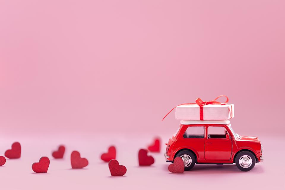 Red toy car delivering carrying on roof gift box with small red hearts on pink background. Valentine's day concept. Banner