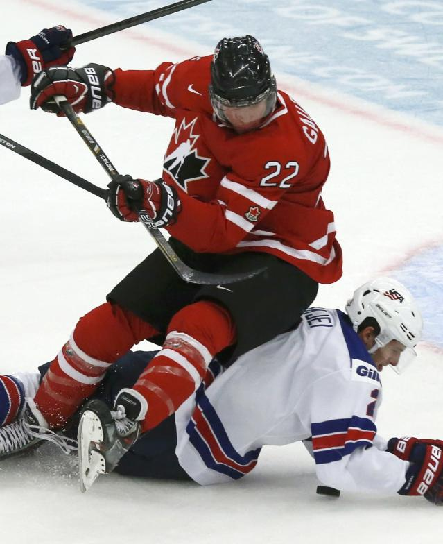 Canada's Frederik Gauthier (22) falls on United States Brady Skjei during the first period of their IIHF World Junior Championship ice hockey game in Malmo, Sweden, December 31, 2013. REUTERS/Alexander Demianchuk (SWEDEN)