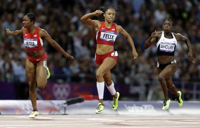 United States' Allyson Felix, center, crosses the finish line to win the women's 200-meters final ahead of compatriot Carmelita Jeter, left, and Ivory Coast's Murielle Ahoure during the athletics in the Olympic Stadium at the 2012 Summer Olympics, London, Wednesday, Aug. 8, 2012. (AP Photo/Lee Jin-man)