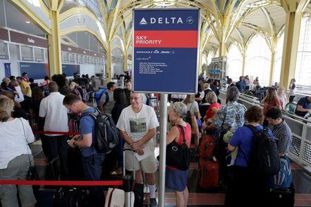 Passengers wait in line to check in after Delta Air Lines computer systems crashed leaving passengers stranded at airports around the globe as flights were grounded at Ronald Reagan Washington National Airport in Washington.