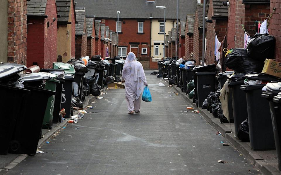 A resident walks past overflowing refuse bins in the Beeston area of Leeds - Christopher Furlong/Getty News