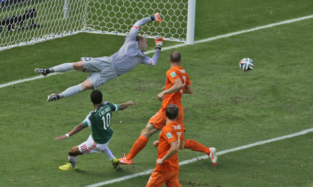 Mexico's Giovani dos Santos, left, shoots past the goal of Netherlands' goalkeeper Jasper Cillessen, back, during the World Cup round of 16 soccer match between the Netherlands and Mexico at the Arena Castelao in Fortaleza, Brazil, Sunday, June 29, 2014. (AP Photo/Themba Hadebe)
