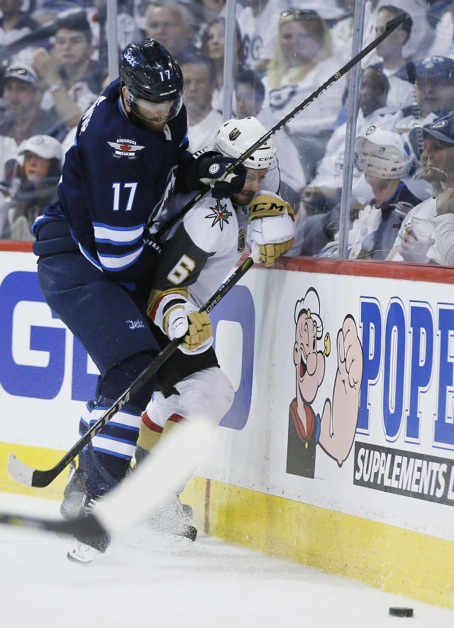 Winnipeg Jets' Adam Lowry (17) checks Vegas Golden Knights' Colin Miller (6) during the second period of Game 1 of the NHL hockey playoffs Western Conference final, Saturday, May 12, 2108, in Winnipeg, Manitoba. (John Woods/The Canadian Press via AP)