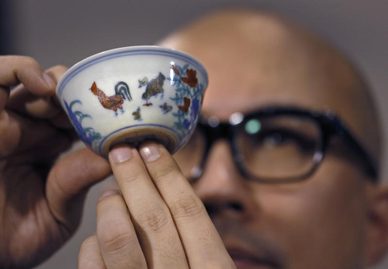 "Sotheby's Deputy Chairman for Asia Nicholas Chow presents the Meiyintang ""Chicken Cup"" from the Chinese Ming Dynasty (1368-1644) during a press conference in Hong Kong, Tuesday, April 8, 2014. Sotheby's said Shanghai collector Liu Yiqian won the bidding for the ""Chicken Cup,"" which is decorated with a rooster, hen and their chicks. Including the auction house's commission, the price for the small cup comes to HK$281.2 million (US$36.1 million), which Sotheby's said is a world record price for Chinese porcelain. (AP Photo/Vincent Yu)"