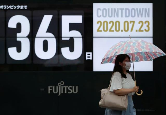 A woman wearing a protective face mask walks past a screen showing a countdown of the days to the Tokyo 2020 Olympic Games amid the coronavirus disease (COVID-19) outbreak, in Tokyo