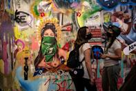 Women view exhibits of street art at the Social Uprising Museum in Santiago