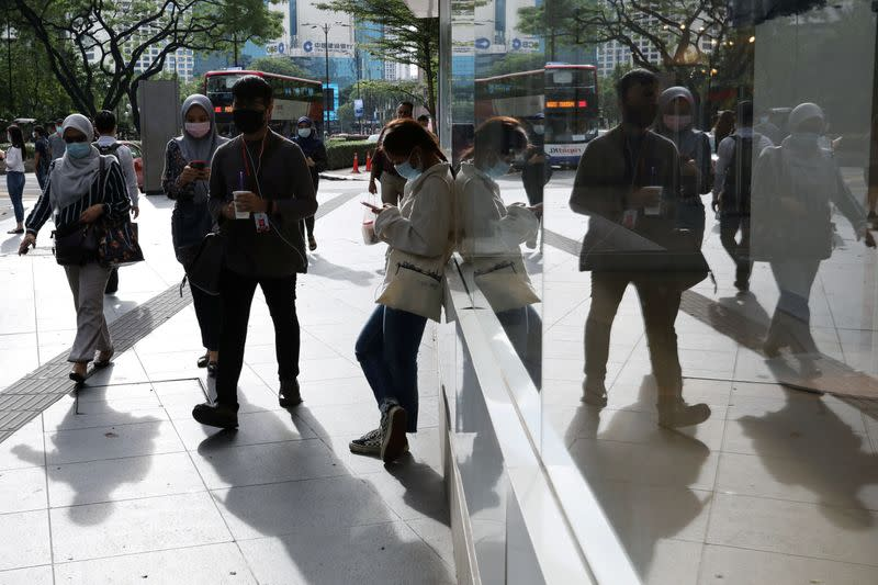 People wearing protective masks are reflected in a glass as they walk outside a shop, amid the coronavirus disease (COVID-19) outbreak in Kuala Lumpur