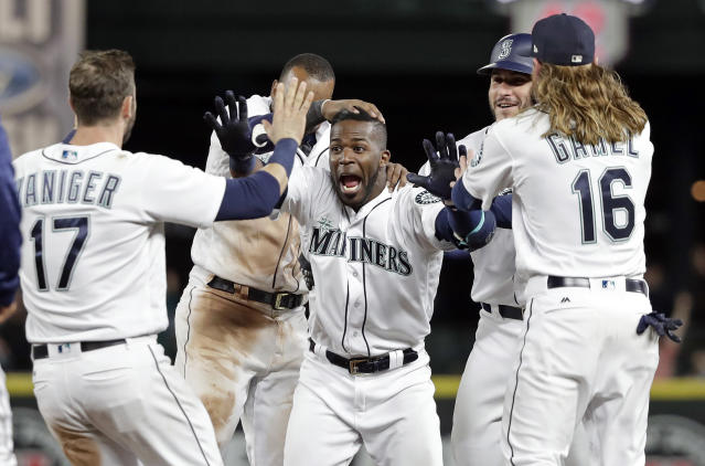 Seattle Mariners' Guillermo Heredia, center, is cheered by teammates after hitting a one-run single to beat the Texas Rangers in the 11th inning of a baseball game Tuesday, May 15, 2018, in Seattle. The Mariners won 9-8. (AP Photo/Elaine Thompson)