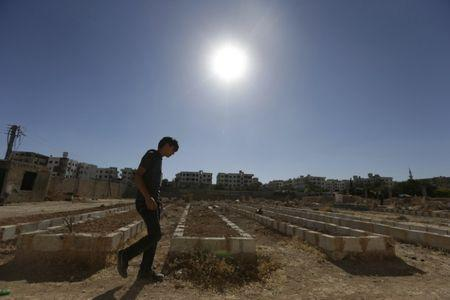 A man walks beside mass graves of people who died during chemical attacks on Zamalka, in Eastern Ghouta, a suburb of Damascus