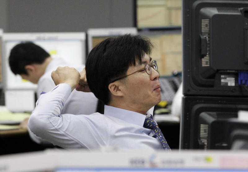 A currency trader stretches during a morning session at the foreign exchange dealing room of the Korea Exchange Bank headquarters in Seoul, South Korea, Monday, June 18, 2012. Asian stock markets climbed Monday after elections in Greece eased fears of global financial turmoil, but analysts warned that the economic crisis shaking the 17 nations in the euro common currency was far from over. (AP Photo/Ahn Young-joon)