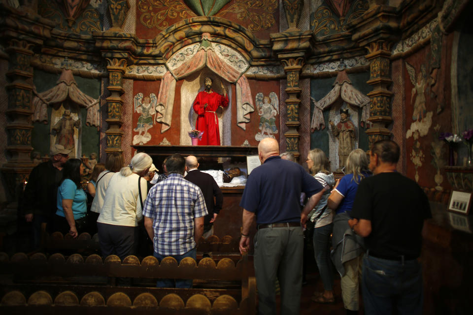 People visit the main church at the Mission San Xavier del Bac in Tucson, Ariz., Friday, Feb. 21, 2020. It was founded as a Catholic mission by Father Eusebio Kino in 1692 when Southern Arizona was part of New Spain. (AP Photo/Dario Lopez-MIlls)