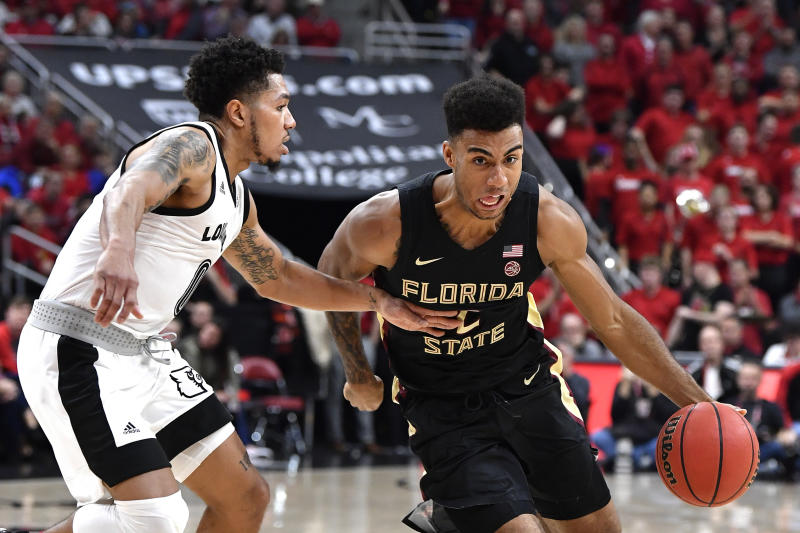 Florida State guard Anthony Polite (2) attempts to get away from the defense of Louisville guard Lamarr Kimble (0) during the first half of an NCAA college basketball game in Louisville, Ky., Saturday, Jan. 4, 2020. (AP Photo/Timothy D. Easley)