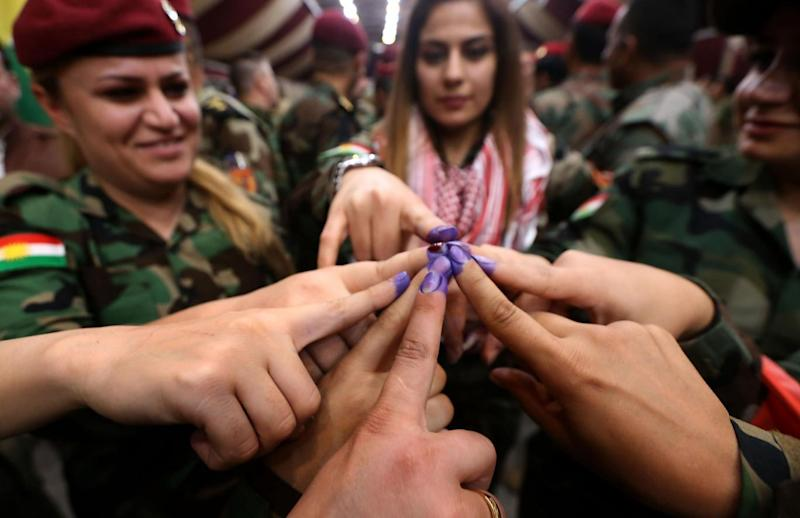 Members of a Kurdish Peshmerga battalion show their ink-stained fingers after casting their vote(AFP/Getty)