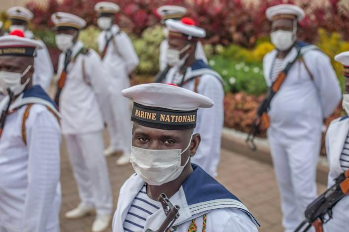 Member of Benin's navy stand easy outside the presidency in Cotonou on Saturday ahead of independence day celebrations