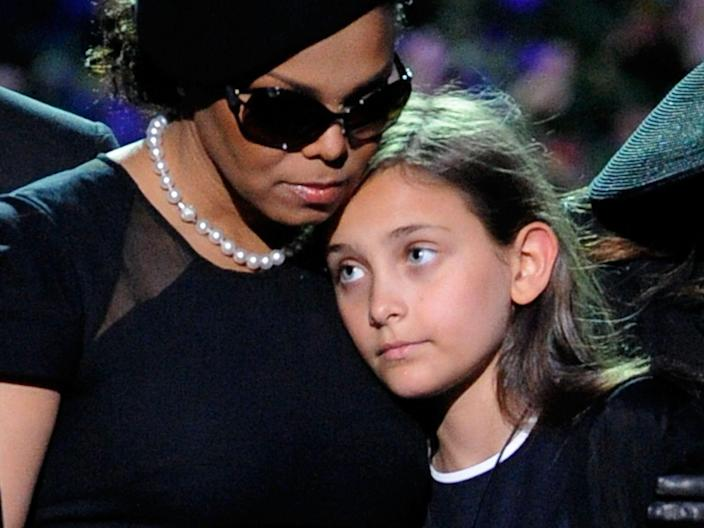 Paris Jackson leaning on Janet Jackson while in attendance at a memorial service for Michael Jackson in July 2009.