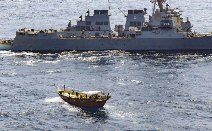 In this Friday, Feb. 12, 2021 photo released by the U.S. Navy, the guided-missile destroyer USS Winston S. Churchill boarded a stateless dhow off the coast of Somalia and interdicted an illicit shipment of weapons and weapon components. The U.S. Navy said on Tuesday, Feb. 16 that it seized a large cache of weapons, including Kalashnikov-style rifles and rocket-propelled grenade launchers, being smuggled by ships off the coast of Somalia. (Mass Communication Specialist 3rd Class Louis Thompson Staats IV/U.S. Navy via AP)