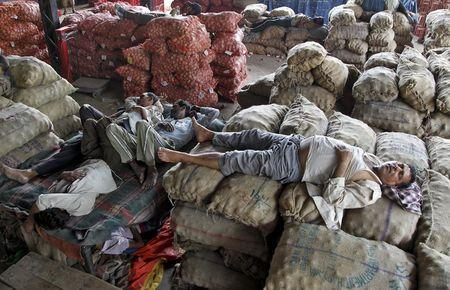 Vendors take a nap on stacked sacks of vegetables at a wholesale market on a hot summer day in Chandigarh, India, May 29, 2015. REUTERS/Ajay Verma