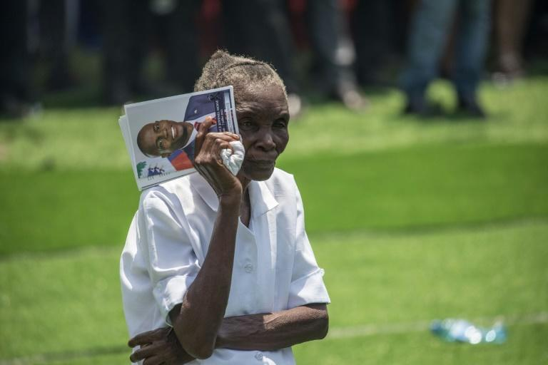 A woman holds a picture of slain Haitian President Jovenel Moise during his funeral on July 23, 2021, in Cap-Haitien, Haiti (AFP/Valerie Baeriswyl)