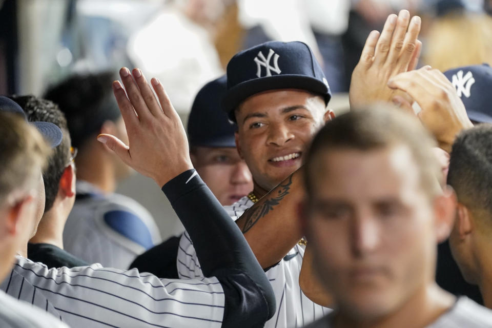 New York Yankees pitcher Luis Gil is congratulated by teammates as he comes into the dugout after pitching during the sixth inning of the team's baseball game against the Baltimore Orioles, Tuesday, Aug. 3, 2021, in New York. Gil gave up four hits and no runs in his six innings. (AP Photo/Mary Altaffer)