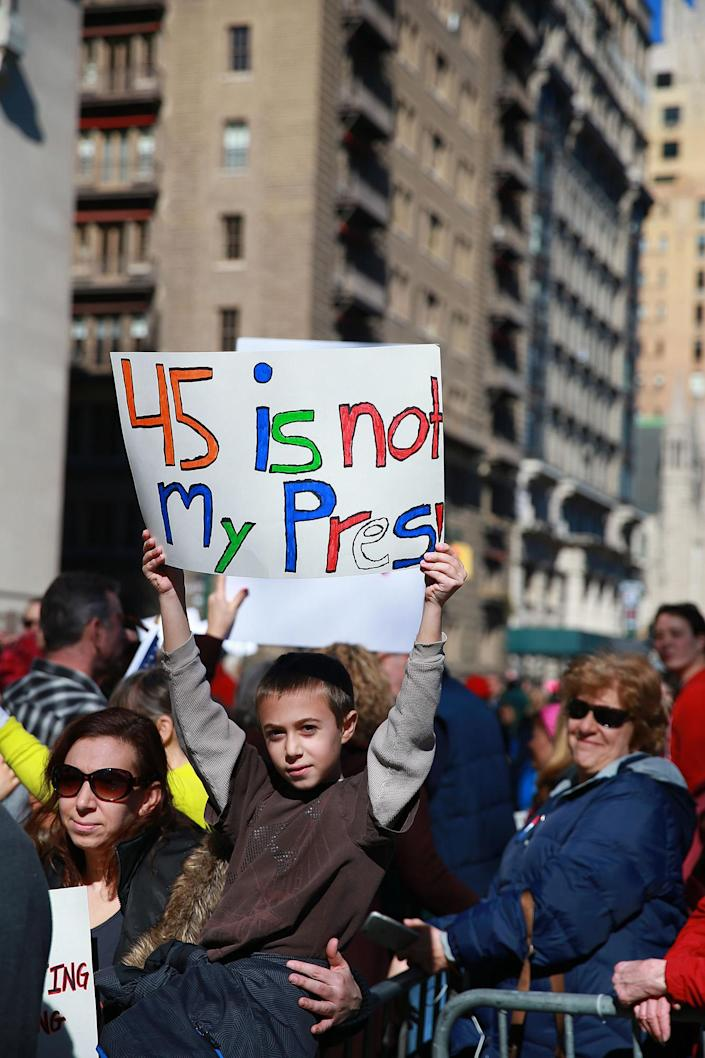 """<p>A youngster with his mother holds up a sign during the """"Not My President's Day"""" rally at Central Park West in New York City on Feb. 20, 2017. (Gordon Donovan/Yahoo News) </p>"""