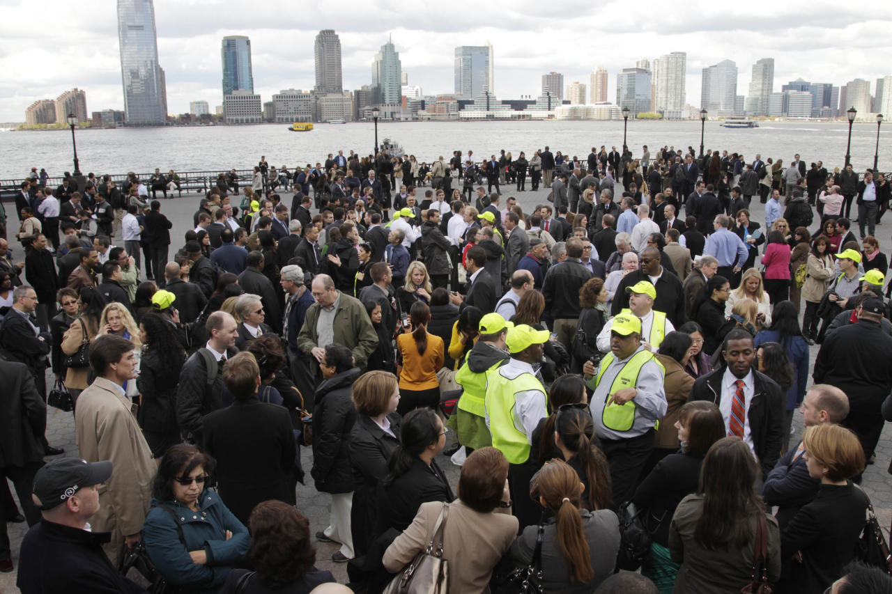 Office workers stand outside Two World Financial Center after it was briefly evacuated in New York, Thursday, April 12, 2012. Authorities say an evacuation was ordered as a precaution at a World Financial Center building after a security guard reported a package that seemed suspicious. (AP Photo/Seth Wenig)