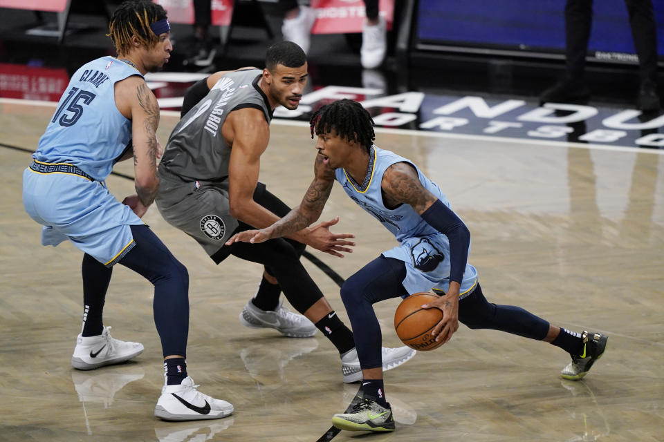 Ja Morant, right, drives past Brooklyn Nets guard Timothe Luwawu-Cabarrot (9) as Grizzlies forward Brandon Clarke (15) sets a screen during the first half of an NBA basketball game Monday, Dec. 28, 2020, in New York. (AP Photo/Kathy Willens)
