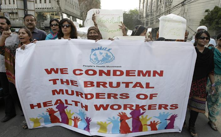 """Pakistani activists rally in Karachi Pakistan to condemn killings of health workers, on Thursday, Dec. 20, 2012. Thousands of polio workers escorted by police guards pressed on with a vital immunization program in Pakistan's second largest city Thursday despite the deaths of nine people gunned down by suspected militants while working on the campaign elsewhere in the country. Placard on top reads """"save Pakistani children."""" (AP Photo/Fareed Khan)"""
