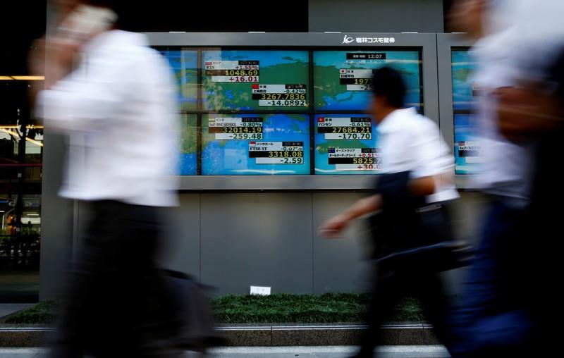 FILE PHOTO: People walk past an electronic board showing Japan's Nikkei average outside a brokerage at a business district in Tokyo