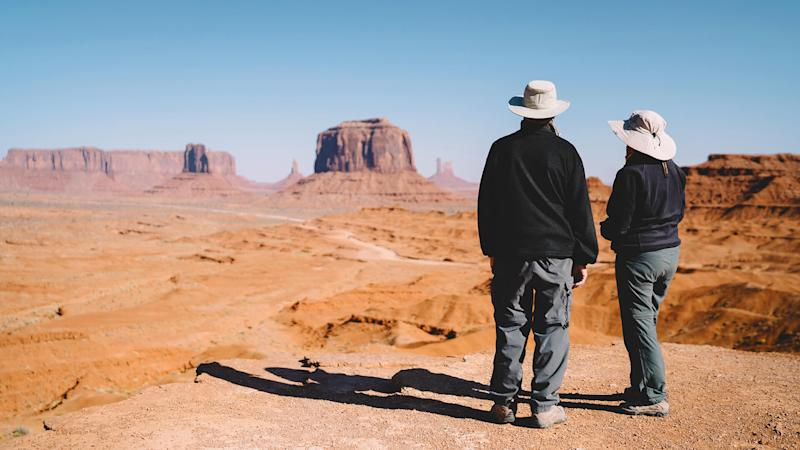 Back view of male and female american tourist observing stone formation in Mountain valley during excursion, couple of travelers standing on viewpoint looking at beautiful landscape in desert.