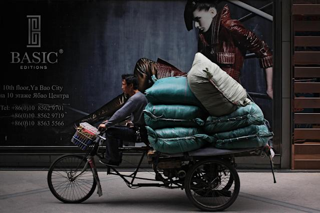 <p>A man rides on a tricycle loaded with goods past by a fashion advertisement billboard at Ritan International Trade Center in Beijing, Monday, May 8, 2017. China has reported its exports expanded for a second straight month in April but at a slower pace while import growth also decelerated as demand cooled both at home and overseas. (AP Photo/Andy Wong) </p>