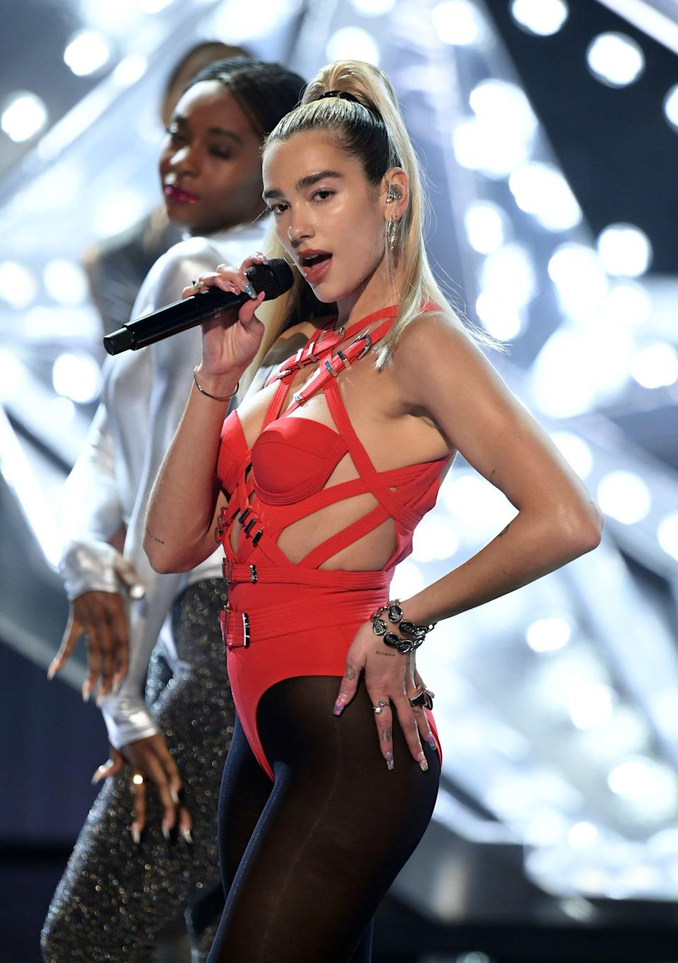 Dua Lipa sings on stage wearing a red leotard with cutouts and black tights.