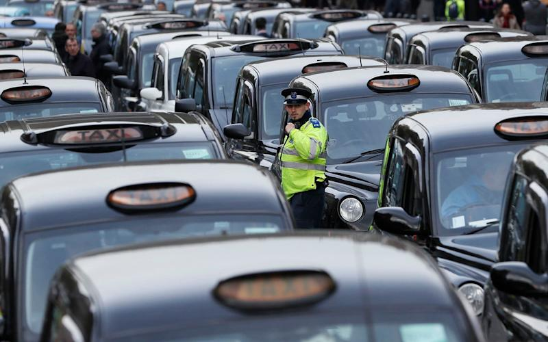 A police officer walks through lines of London's Black Taxis - Credit: Kirsty Wigglesworth/AP