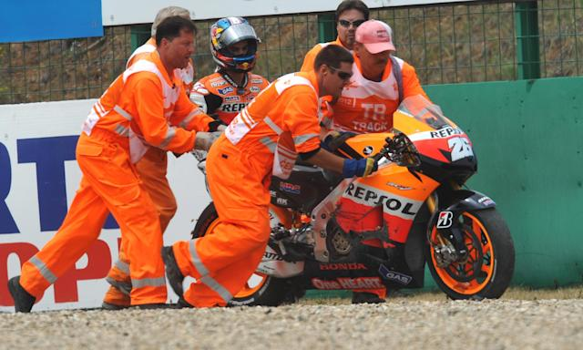 Track marshals push Spain's Dani Pedrosa's Yamaha motorcycle after he falled during the qualifying pratice session of the Czech Republic Grand Prix in Moto GP on August 25, 2012 in Brno ahead of the Grand prix on August 26. Spain's Jorge Lorenzo secured pole position ahead of Enlgand's Cal Crutchlow and Spain's Dani Pedrosa. AFP PHOTO/ MICHAL CIZEKMICHAL CIZEK/AFP/GettyImages