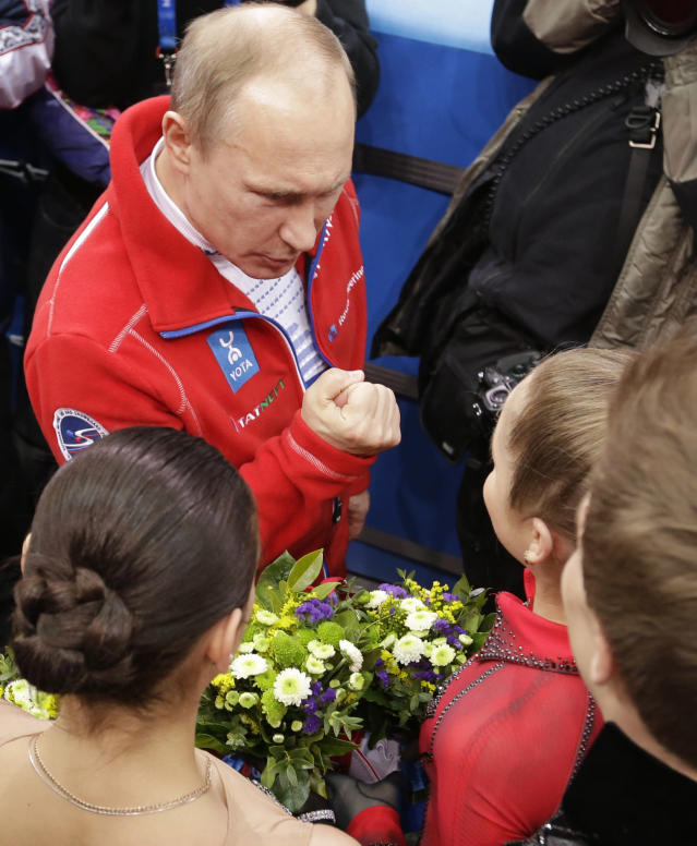 Russian President Vladimir Putin, left, speaks with Julia Lipnitskaia of Russia after Russia placed first in the team figure skating competition at the Iceberg Skating Palace during the 2014 Winter Olympics, Sunday, Feb. 9, 2014, in Sochi, Russia. (AP Photo/David J. Phillip)