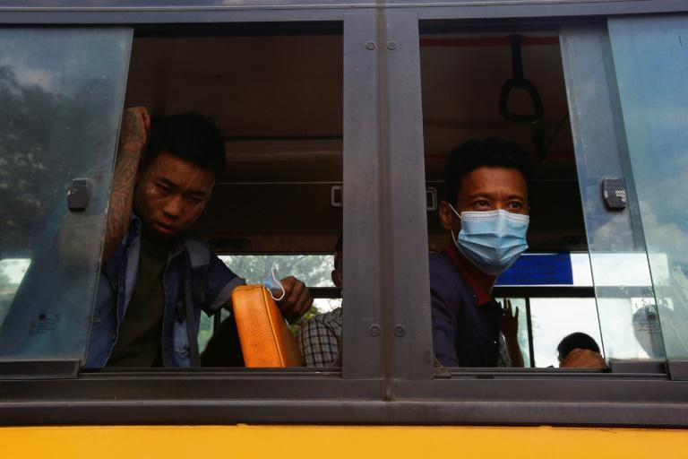 Newly released prisoners look on from a bus outside Insein Prison in Yangon
