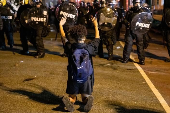A demonstrator confronts police