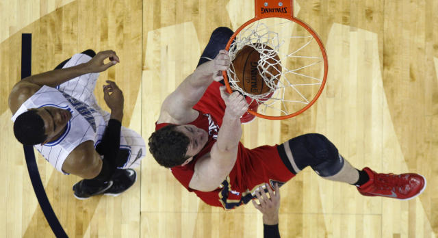 New Orleans Pelicans center Omer Asik slam dunks over Orlando Magic forward Tobias Harris, left, in the first half of an NBA basketball game in New Orleans, Tuesday, Oct. 28, 2014. (AP Photo/Gerald Herbert)