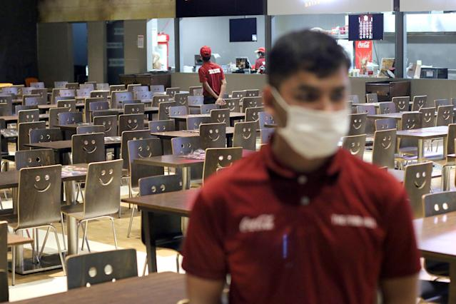 A worker is pictured wearing a mask in an empty restaurant in Dhaka on 23 March. Bangladesh has had 33 confirmed coronavirus cases since the outbreak was identified. (Getty Images)