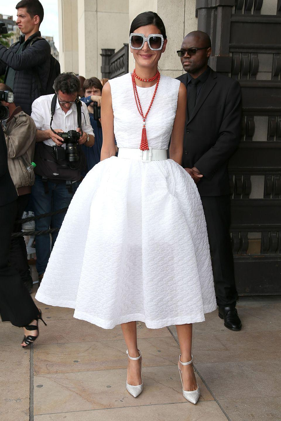 <p>She channelled her inner Audrey Hepburn in a feminine, full-skirted white dress worn with classic white heels and oversized shades in July 2015.</p>