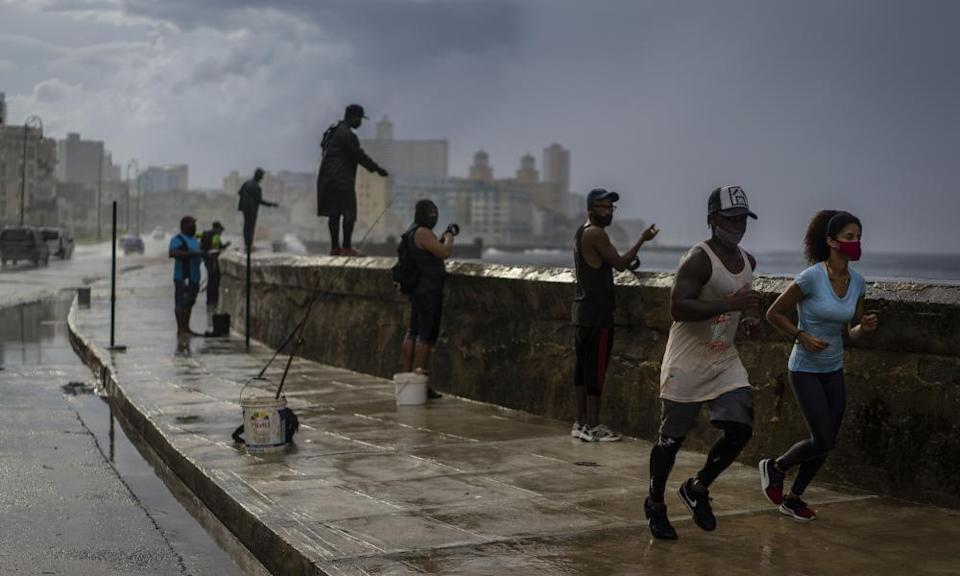 Joggers and fishermen in the rain on the Malecon, Havana famous sea wall.