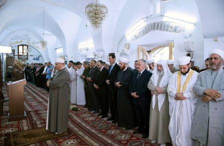 Syria's President Bashar al-Assad (6th L) attends prayers on the first day of the Muslim holiday of Eid al-Fitr, inside a mosque in Hama, in this handout picture provided by SANA on June 25, 2017, Syria. SANA/Handout via REUTERS