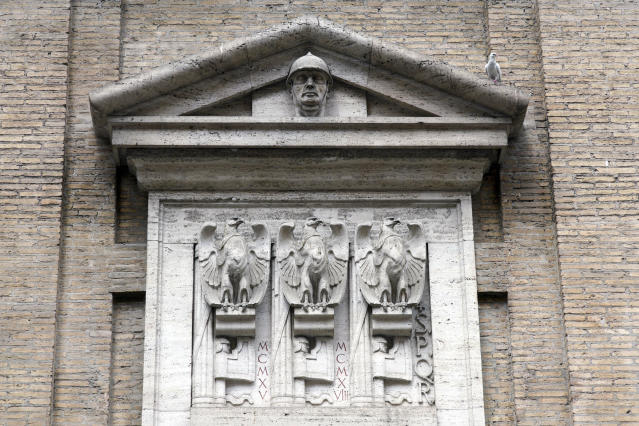 Fasces, the original symbol of Fascism adapted from ancient Rome, showing a bundle of rods tied together around an axe, are seen carved with eagles on the facade of the Madonna dei Monti church, above a plaque commemorating the fallen soldiers of WWI, in downtown Rome, Friday, May 3, 2019. While Germany systematically wiped out traces of Adolf Hitler's Nazi regime after World War II, the legacy of his Axis ally, Benito Mussolini, remains present in Italy even today. (AP Photo/Andrew Medichini)