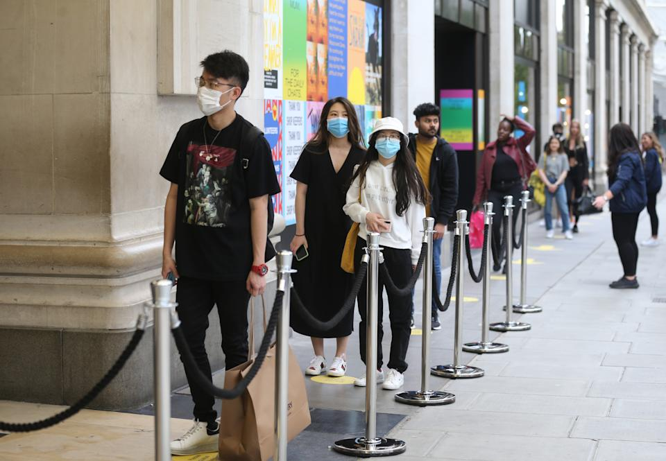 Shoppers queue outside department store Selfridges on Oxford Street, London, as non-essential shops in England open their doors to customers for the first time since coronavirus lockdown restrictions were imposed in March. Picture date: Monday June 15, 2020.